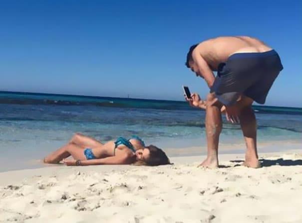 парень фотографирует девушку на песке