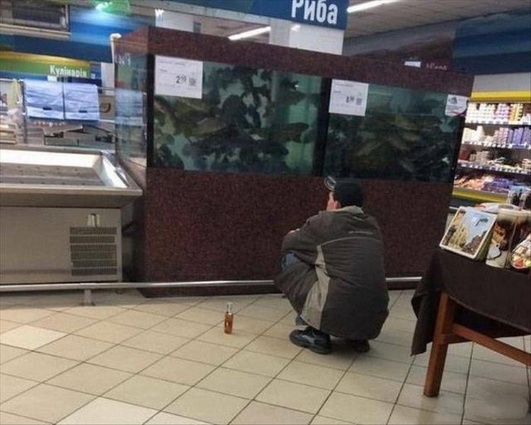 парень сидит перед аквариумом с рыбой