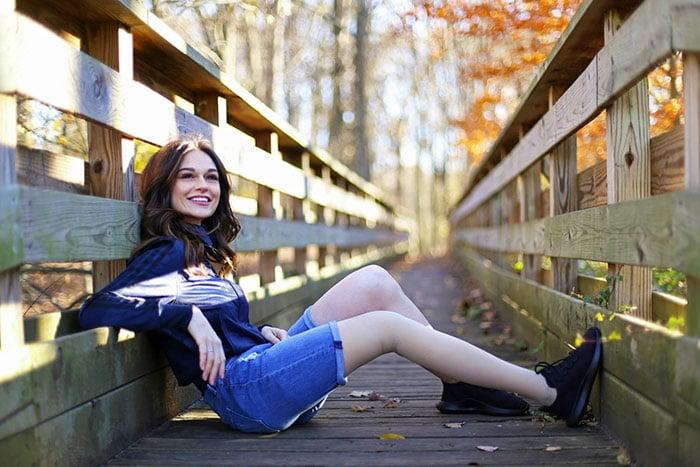 девушка сидит на мостике осенью
