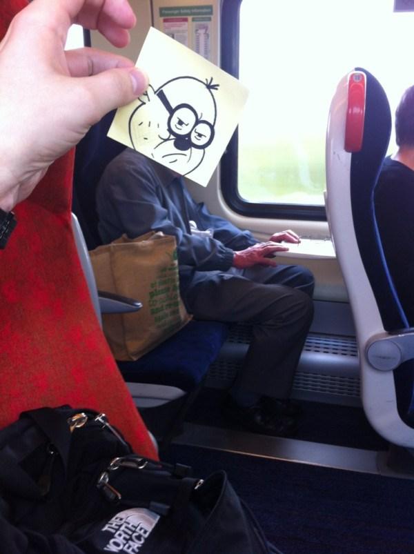 мужчина в поезде с мультяшной головой