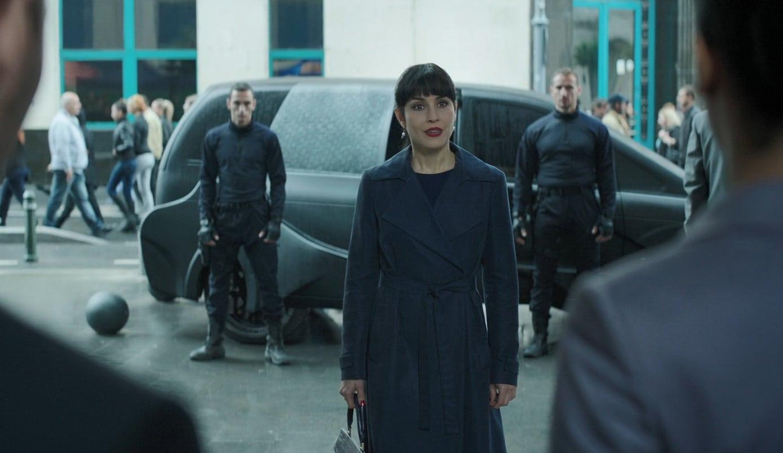 девушка в синем плаще а сзади машина и два охранника