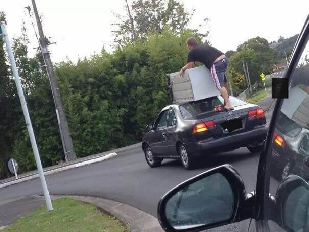 мужчина едет на машине с холодильником