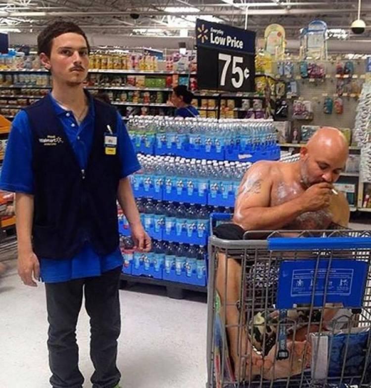 мужчина сидит в тележке в супермаркете