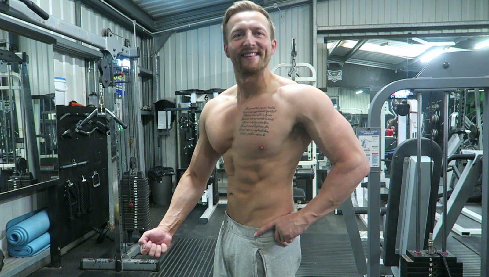 мужчина с мускулами качается в тренажерном зале