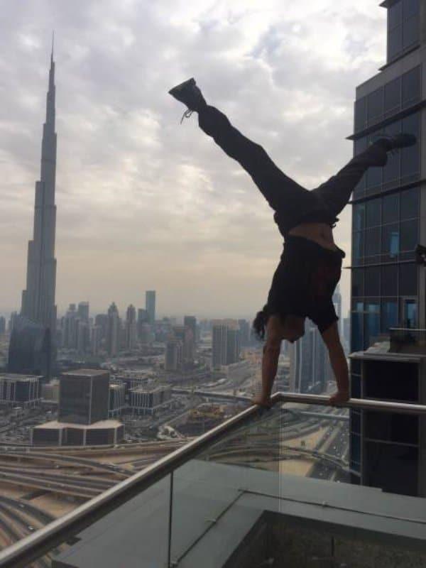парень стоит на руках на перилах балкона