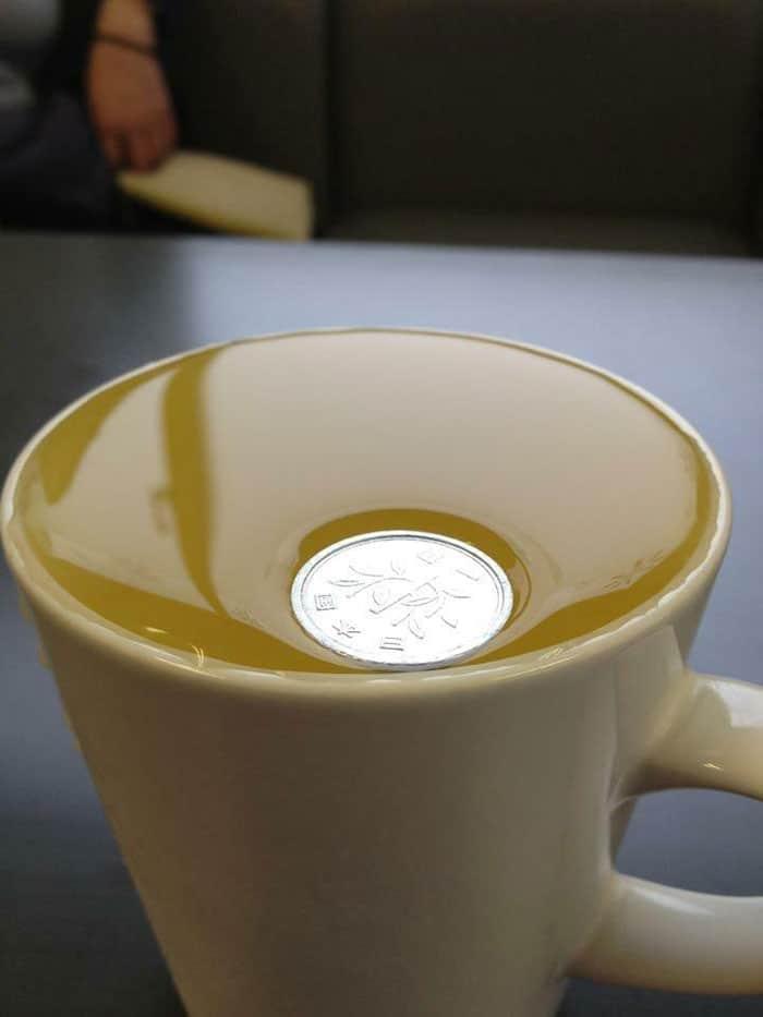 монета в кружке с напитком
