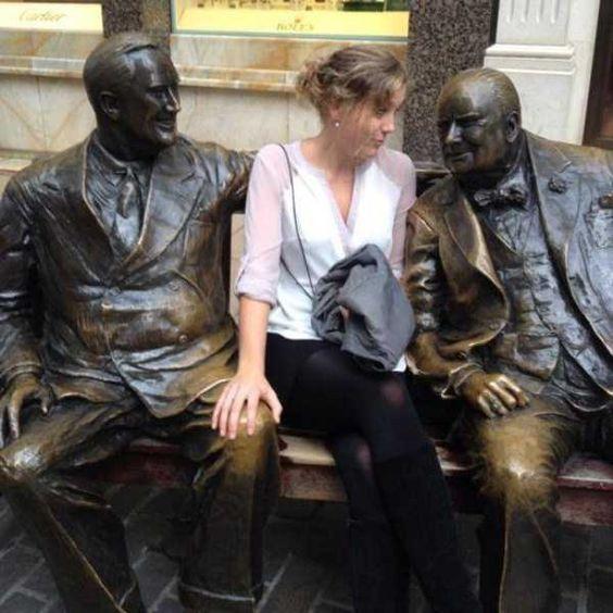 девушка сидит рядом со скульптурой мужчинам
