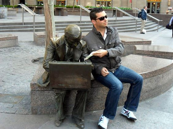 парень сидит рядом со скульптурой