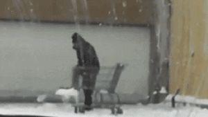 мужчина собирает лопатой снег