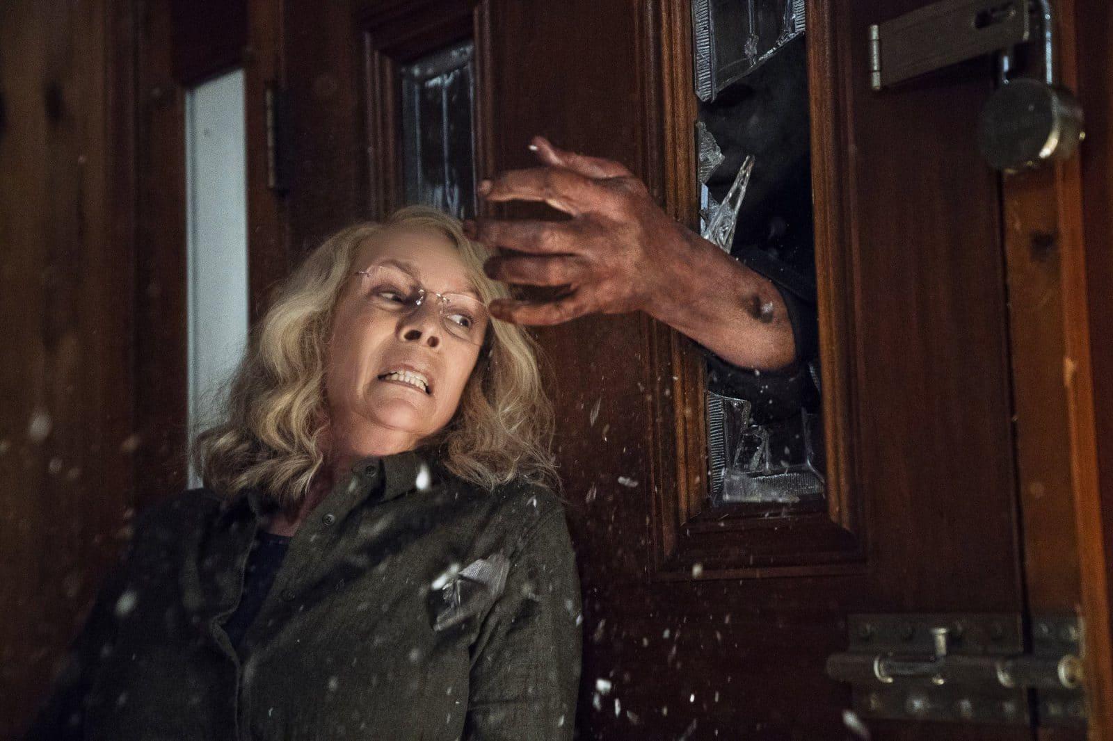 женщина в страхе перед рукой разбившей в двери стекло