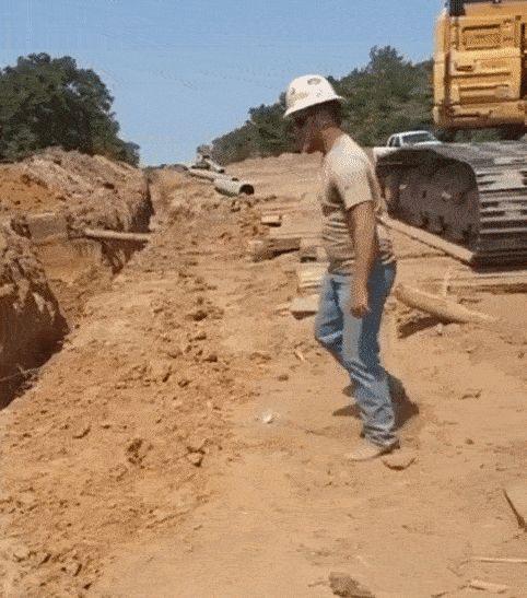 строитель перепрыгивает яму