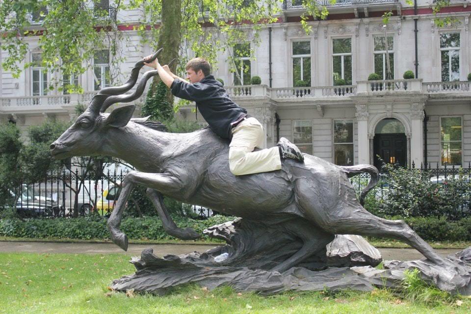 парень верхом на памятнике антилопе