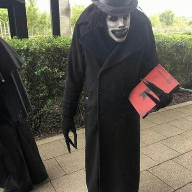 человек в гриме и черном пальто