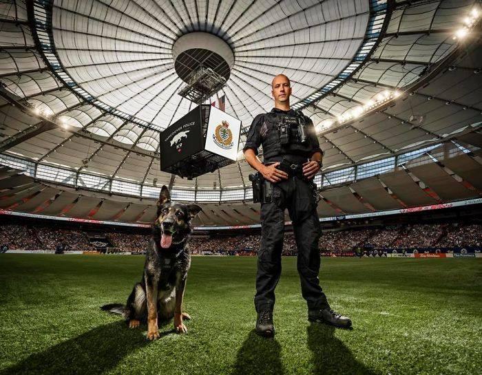 полицейский с собакой на футбольном поле