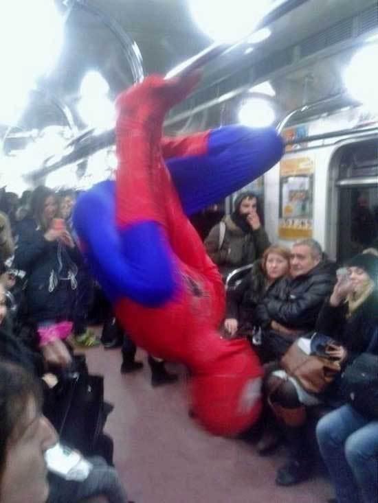 человек-паук висит на поручне в метро