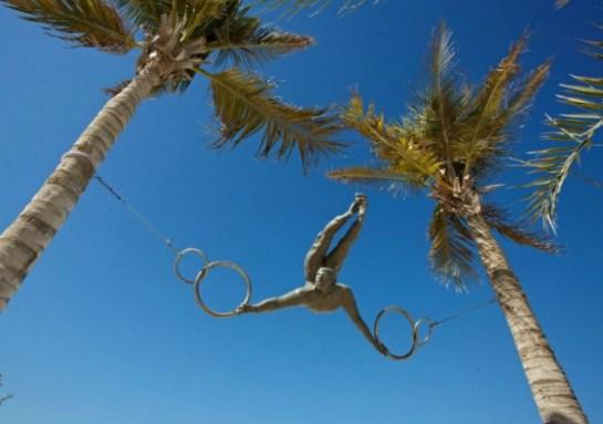 скульптура воздушного гимнаста между пальмами