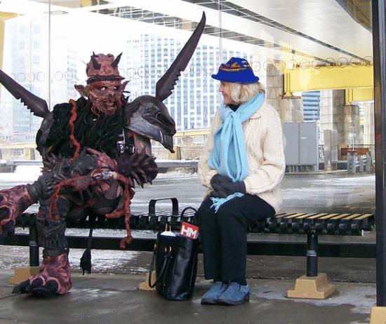 человек в костюме монстра на остановке