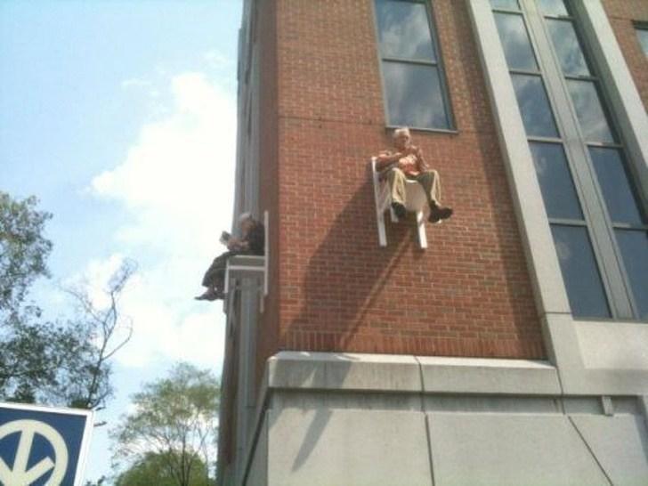 мужчина сидит на стуле прямо на здании