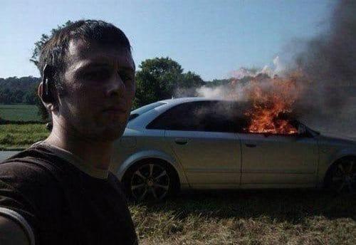 мужчина делает селфи на фоне горящей машины