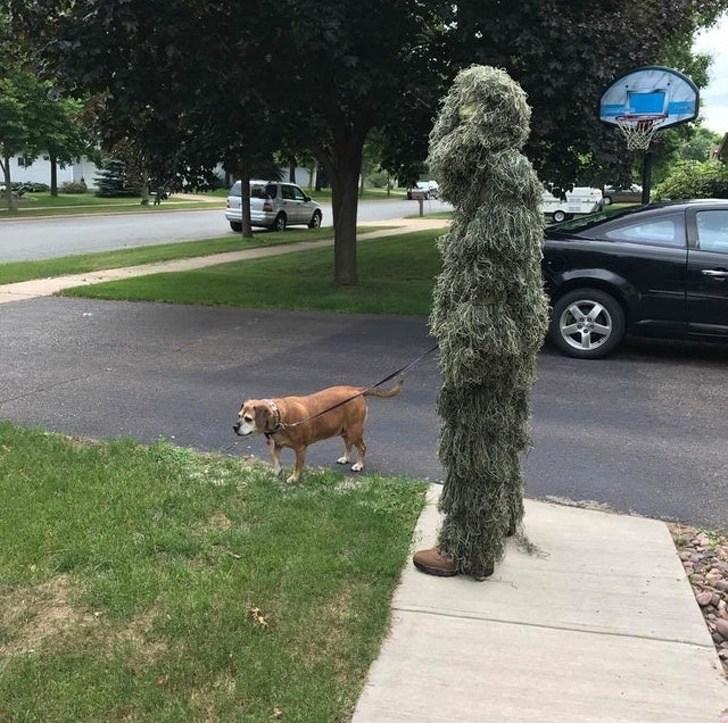 человек в странном костюме с собакой