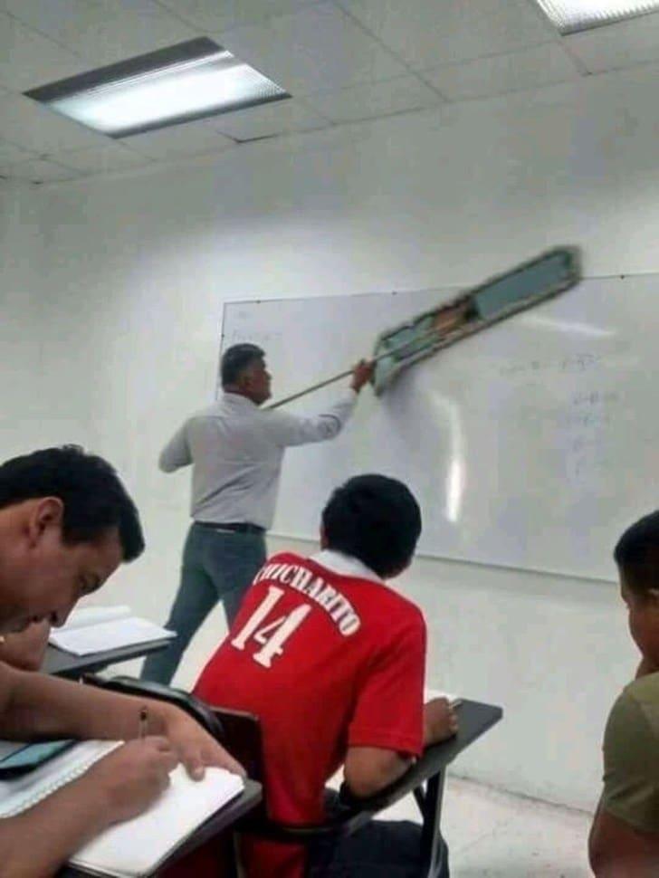 преподаватель вытирает доску шваброй