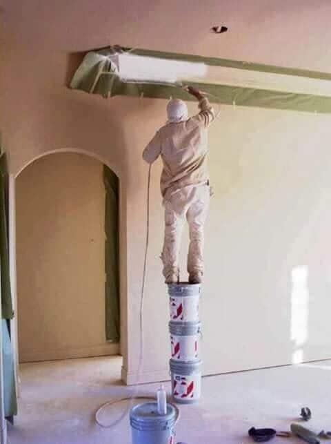 мужчина стоит на банках краски