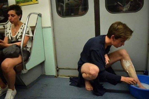 парень бреет ноги в метро