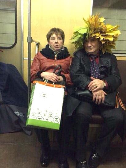 женщина сидит в метро с мужчиной у которого на голове листья