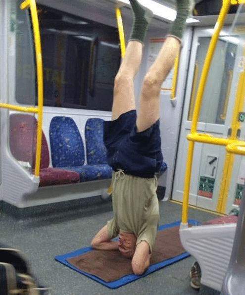 мужчина стоит на голове в метро