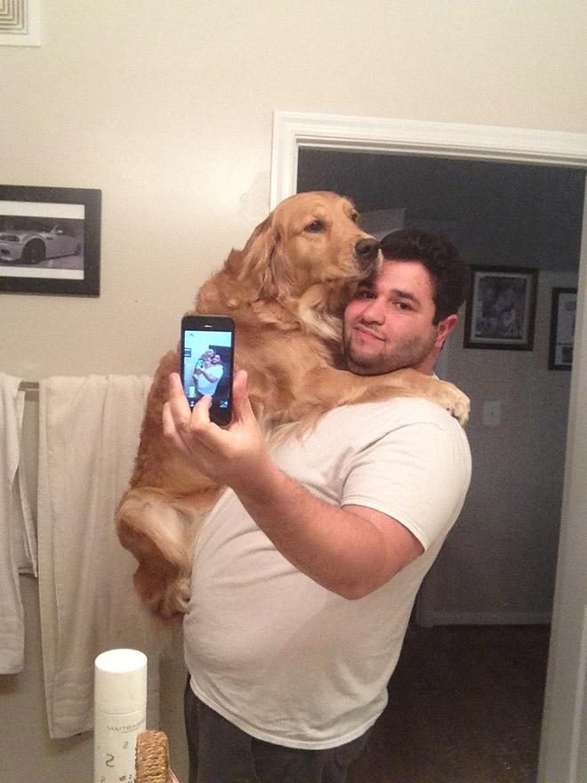 мужчина держит на руках собаку