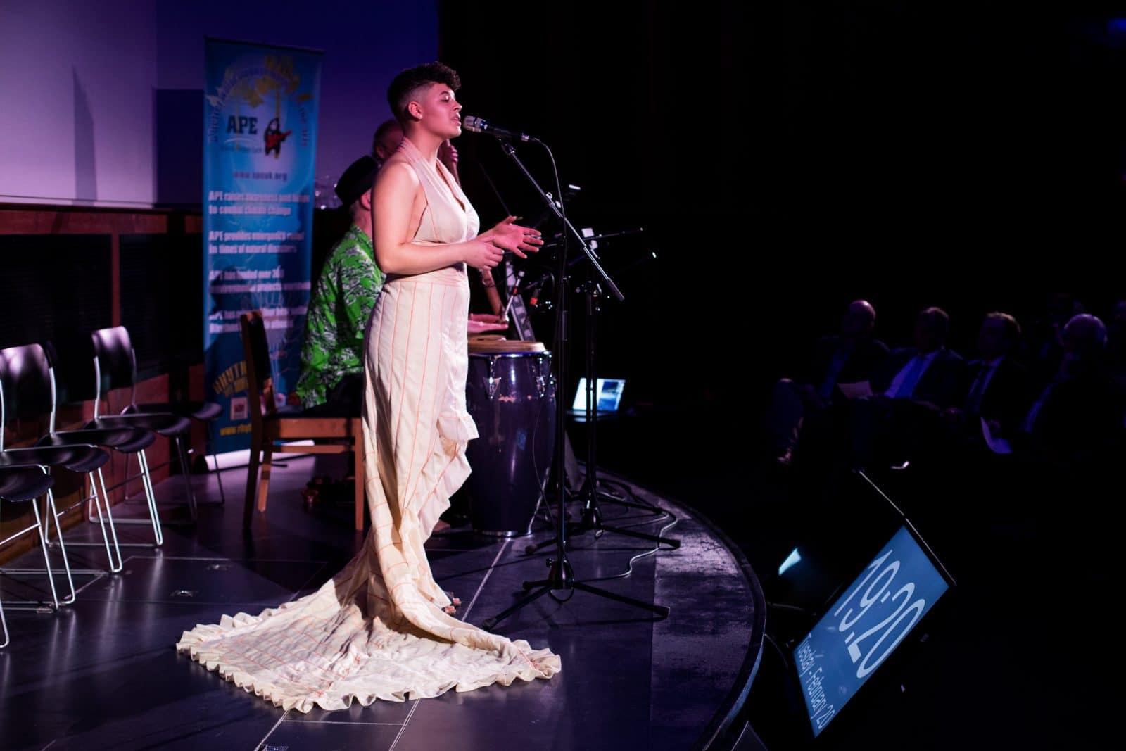 женщина в розовом платье у микрофона