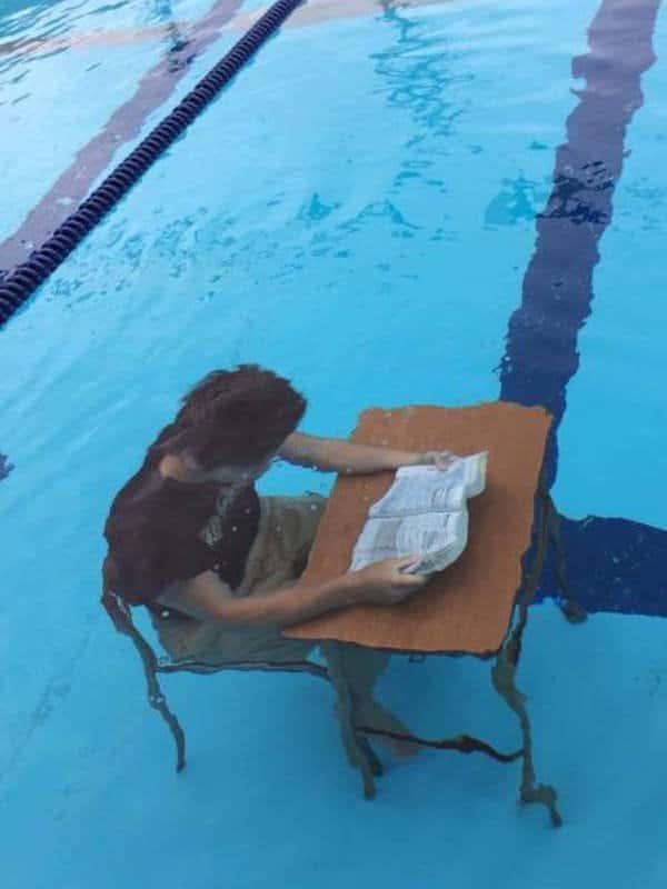 парень за партой под водой