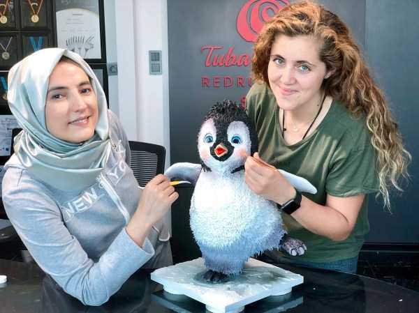 девушки рядом с тортом в форме пингвина