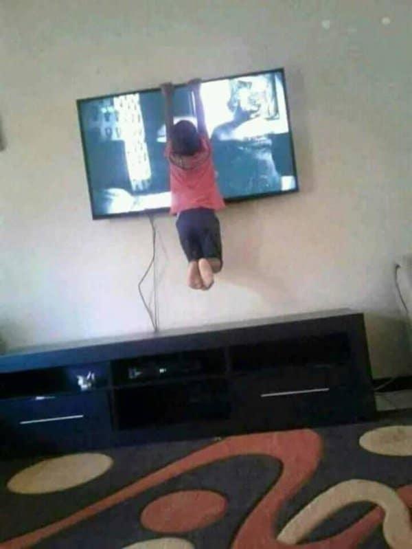 мальчик висит на плазменном телевизоре