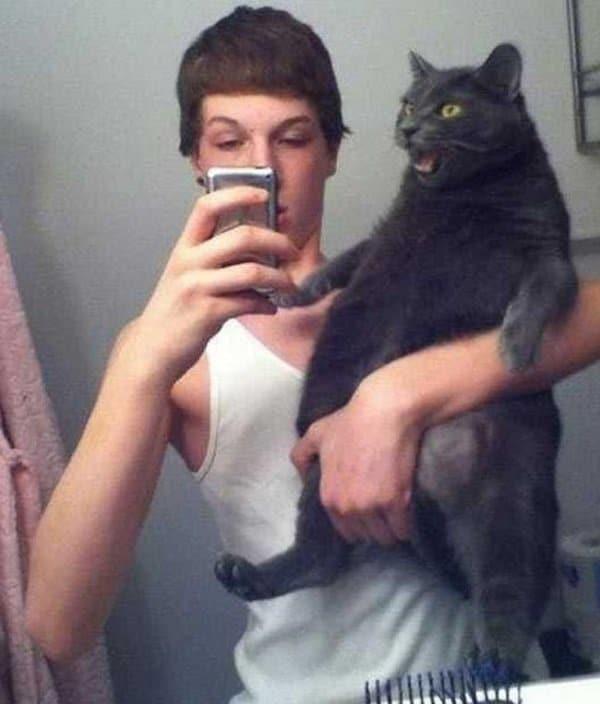 парень с котом на руках делает селфи