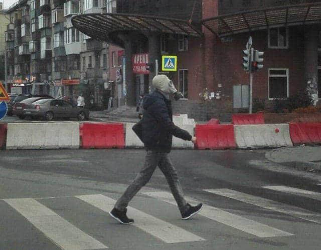мужчина в противогазе на пешеходном переходе