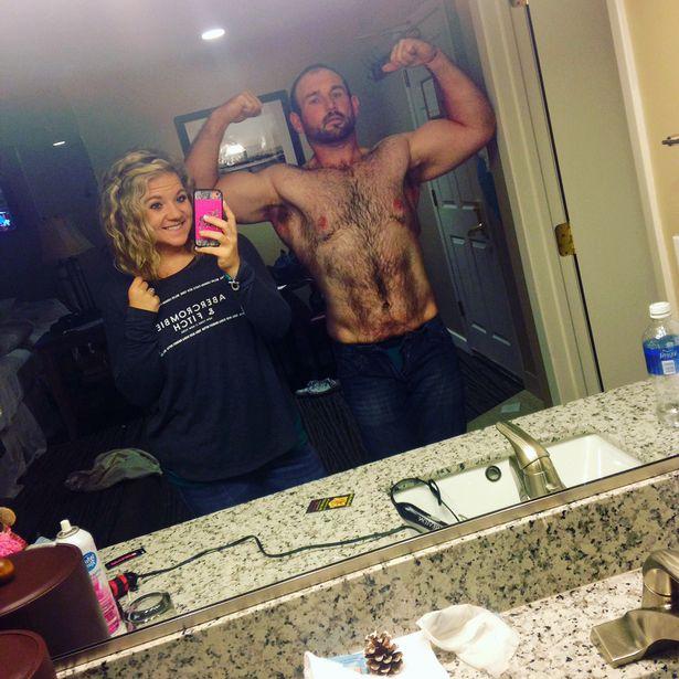 мужчина показывает бицепсы в зеркале и девушка со смартфоном