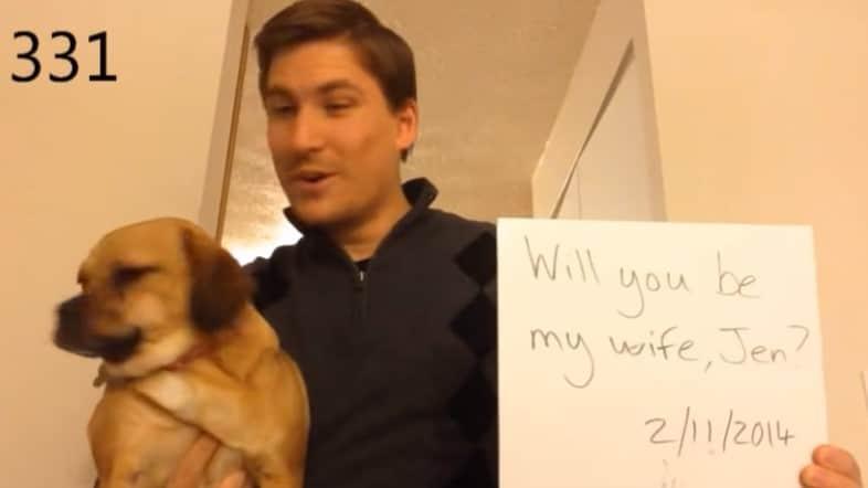 """мужчина с собакой и листом бумаги со словами """"Выходи за меня замуж"""""""