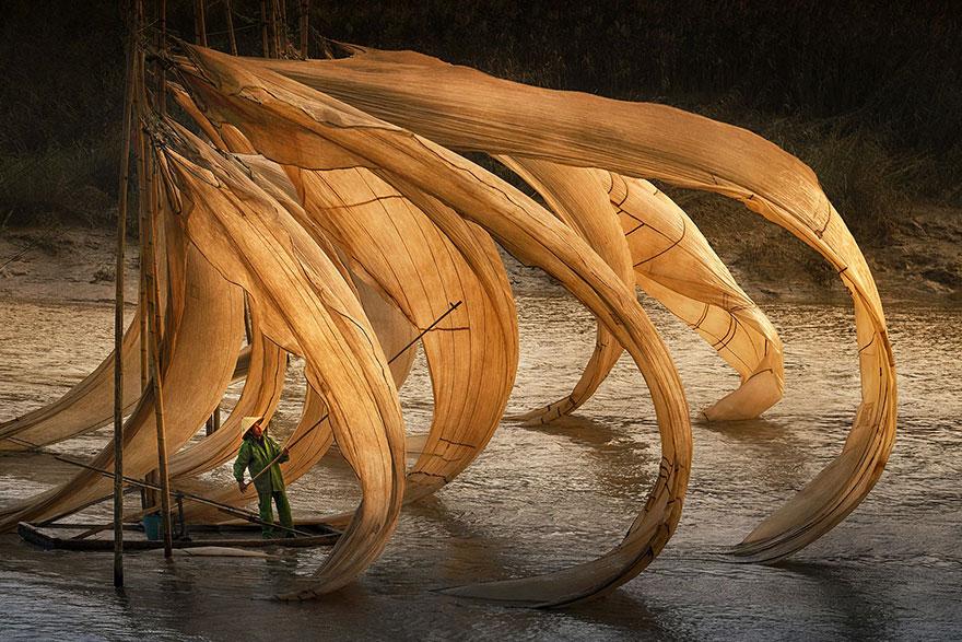 рыбак с большими парусами и сетями на воде