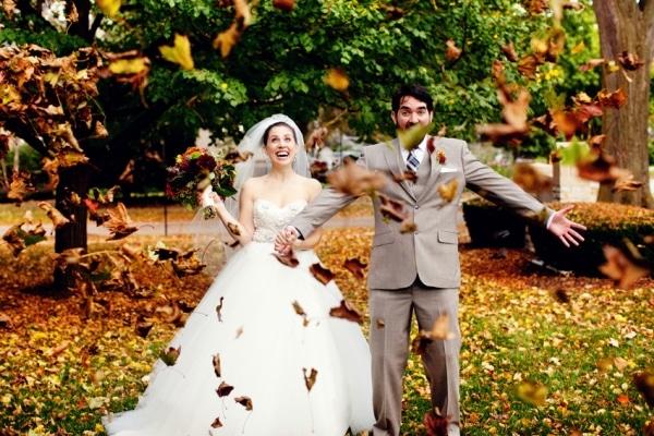 невеста и жених бросают осенние листья