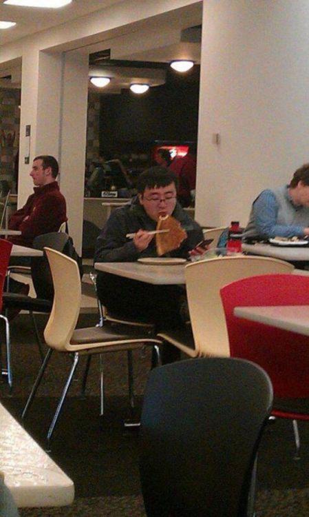 парень ест пиццу палочками