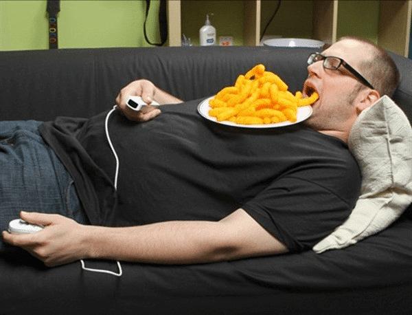 мужчина ест, лежа на диване