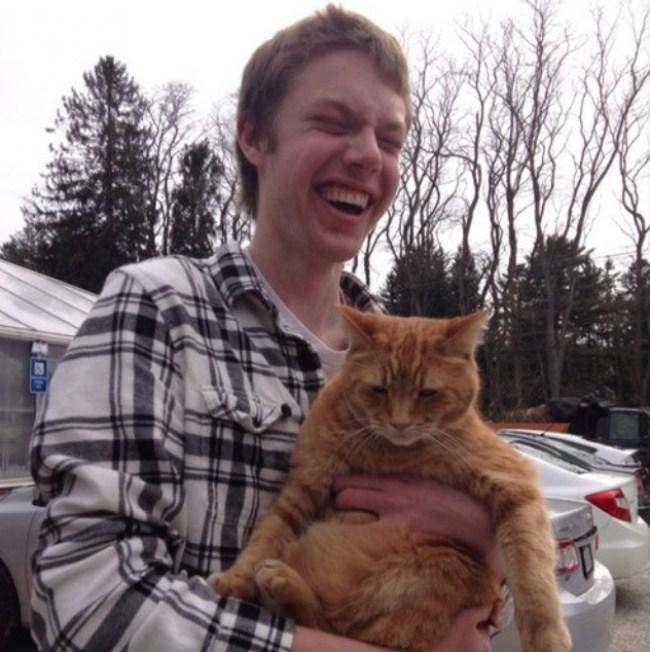 парень держит рыжего кота
