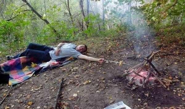 мужчина лежит у костра
