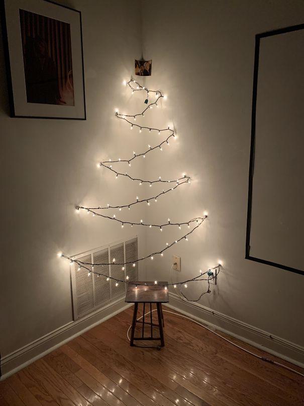 елка из гирлянды в углу комнаты