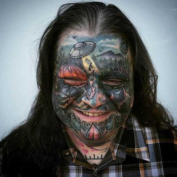 мужчина с лицом в татуировках