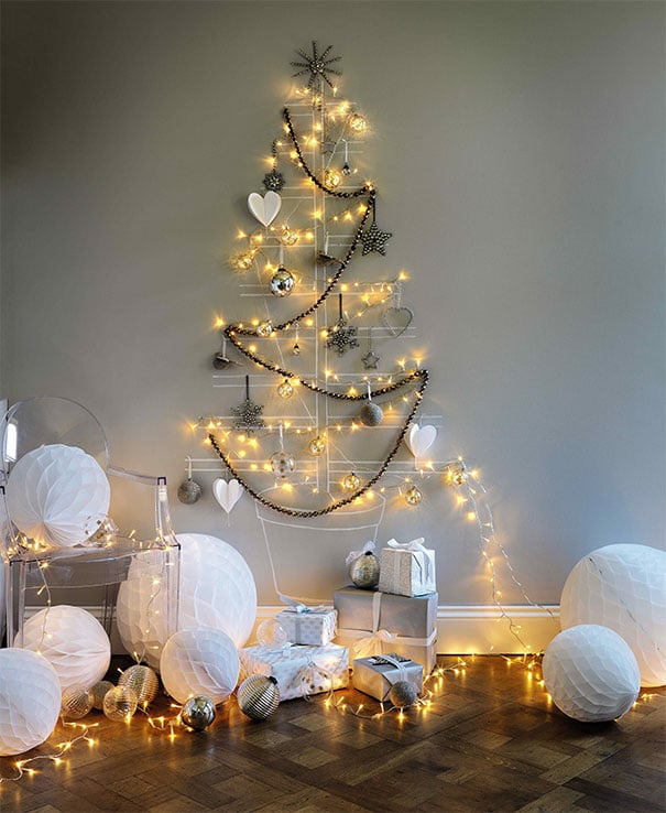 елка из гирлянд и игрушек на стене