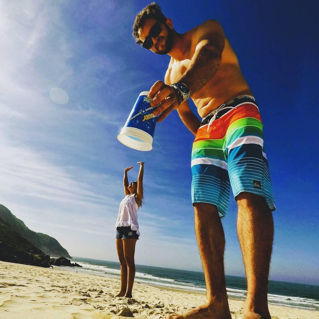 парень накрывает стаканом девушку на пляже