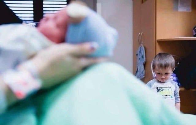 старший брат смотрит на новорожденного