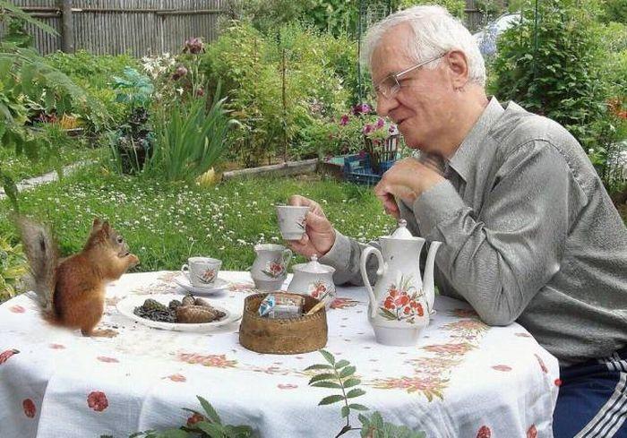 пожилой мужчина за столом с белкой
